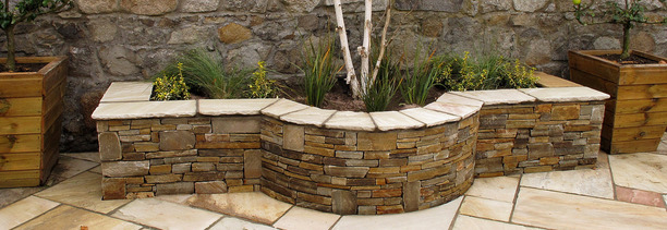 A beautiful Raised Planting Bed constructed with Donegal Quartz stone with a Sandstone wall capping | Owen Chubb Garden Landscapers